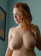 Curvy redhead with tattoos and huge tits posing nude