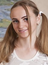 Cute teen with pigtails spreading on the couch
