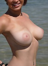 Cute redhead shows off her big tits at the beach