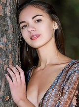 Cute brunette teen stripping in a forest