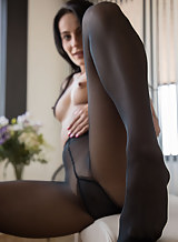 Black-haired girl in pantyhose toying