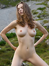 Busty brunette nude on a mountain